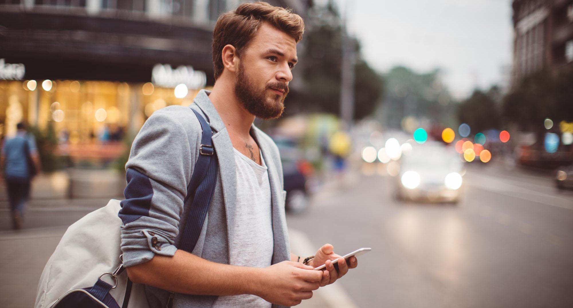junger Mann mit Smartphone in der Stadt